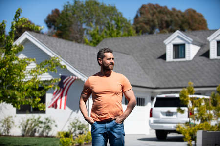 Portrait of laughing guy with hands in pockets leaning against american house. Man standing in front of his new home. Real people.
