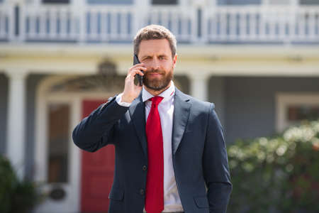 Happy businessman talking on the phone outdoors.
