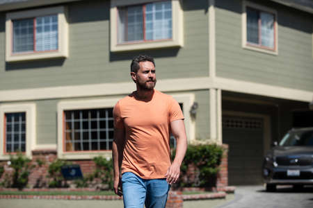 Man businessman in front of house looking up, outdoor portrait.