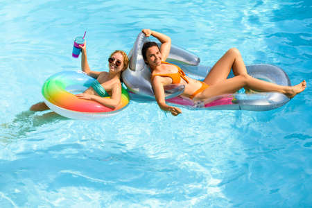 Summer sensual girls in pool. Summertime swimming pool. Summer leisure and holiday. Woman on summer vacation. Girl in swimmsuit. Beach vacation.