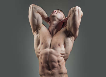 Muscular man athlete. Bodybuilder with muscular athletic body with torso and strong belly with six packs or abs in studio on grey background.