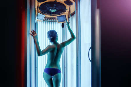 Woman with healthy body in solarium spa salon, has beautiful back and buttocks, copy space.