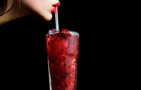 Sensual lips and summer cocktail with strawberry for young girl isolated on black. Thirst and refresh. woman drink cocktail with ice cube, copy space.