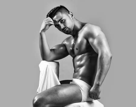 Handsome man or muscular bodybuilder, with sexy, muscle torso, body, with six packs and abs, triceps, biceps, with oily skin in white underpants sits on chair on grey background.