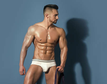 Sexy man isolated full body. Athletic bodybuilder man on blue background. Coach sportsman with chest in pants. Man with muscular wet body and torso hold rubber