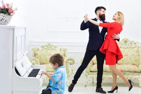 Piano school concept. Child play piano musical instrument, while parents dancing. Parents enjoy parenthood. Kids musician family education concept. Standard-Bild