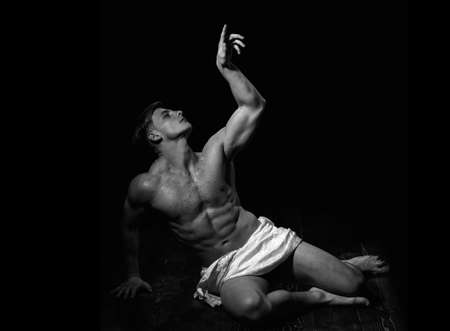 Man with muscular wet body. Art man body. Athletic bodybuilder pose as statue.