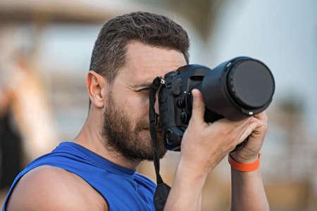 Man professional photographer holding his black digital camera. Stockfoto