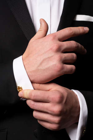Man fixing cufflinks. Gentleman in black suit. Elegant and stylish clothes. Male fashion. Business look. Фото со стока
