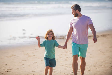Father and son walking on summer beach. Dad and child boy holding hands and walk together. Family travel, vacation, fathers day concept.