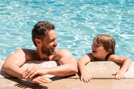 Portrait of father and son relax in swimming pool. Pool resort. Happy family face. Copy space.