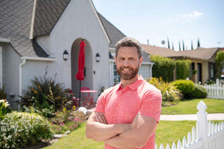 Smiling american man with arms crossed standing in front of his new home. Buy, sell, real estate, property, home insurance concept. Real people. Stock Photo