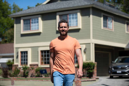 Portrait of confident man standing outside new home. Successful real estate agent purchasing house for investment purpose. Happy and handsome.