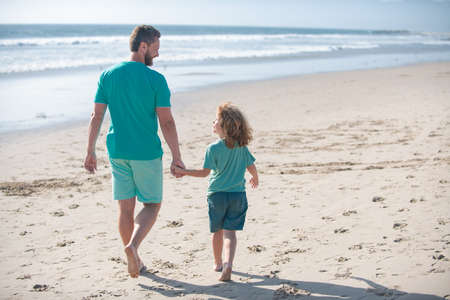 Dad and child boy holding hands and walk together. Father and son walking on summer beach. Concept of friendly family and of summer vacation.