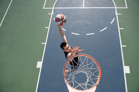 Basketball concept. Man jumping and making a slam dunk playing streetball, basketball. Urban authentic. Reklamní fotografie