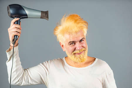 Handsome redhead man with long hair dries his hair with a hairdryer. Blonde man with hair dryer.