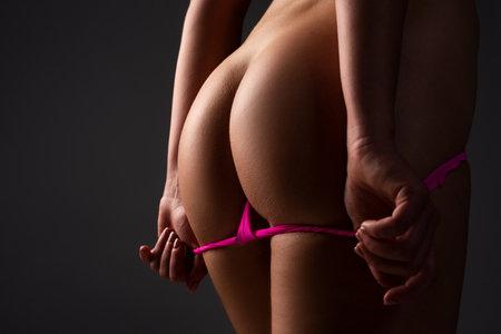 Sexy butt of sensual woman, in bikini, with thong lingerie closeup.