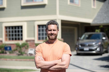 Happy man standing outside house. Confident businessman. Stock Photo