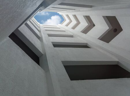 view of an atrium in a building: deep atrium gray building overlooking the blue sky with clouds Stock Photo