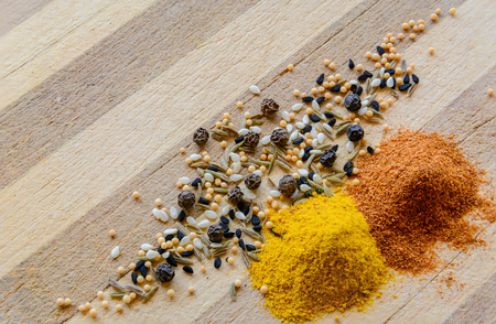 black seeds: Spices sprinkled on a wooden board. Curcuma, black pepper, mustard seeds and black seeds. Stock Photo
