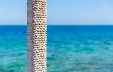 entwined: wooden pole with rope entwined on a background of blue sea and sky