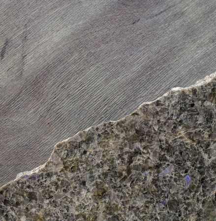 dark polished stone with an irregular fracture in the background ebony. Top view, space for text Stock Photo