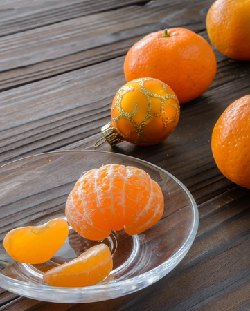 clementines: slices of orange and a ripe tangerine in a glass saucer. Against the background of the old wooden table. View angle of 45 degrees.