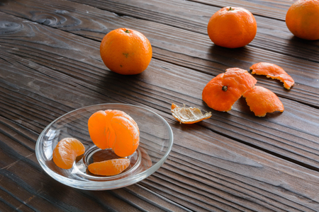 purified: slices of orange and a ripe tangerine in a glass saucer. Against the background of the old wooden table. View angle of 45 degrees.