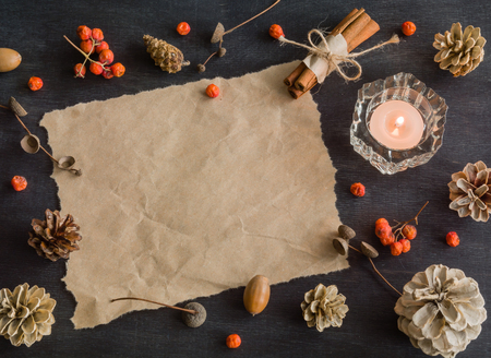 string top: Dark Christmas background with candles and berries of mountain ash. White pine cones and branches with acorns. Cinnamon tied with string. Top view.
