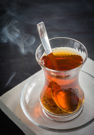 Transparent cup of thin glass and black tea. Spoon into a glass. Empty place