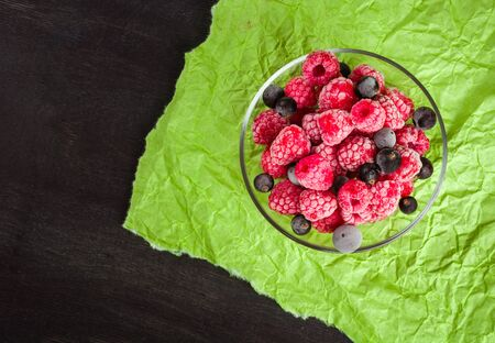 Frozen raspberries in a glass saucer. Frost on the berries. Dark and green background. Green crumpled paper.