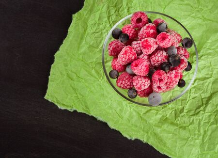 vitamine: Frozen raspberries in a glass saucer. Frost on the berries. Dark and green background. Green crumpled paper.