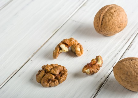 Whole and shelled walnuts on a white wooden background. The core and the shell. Space for text.