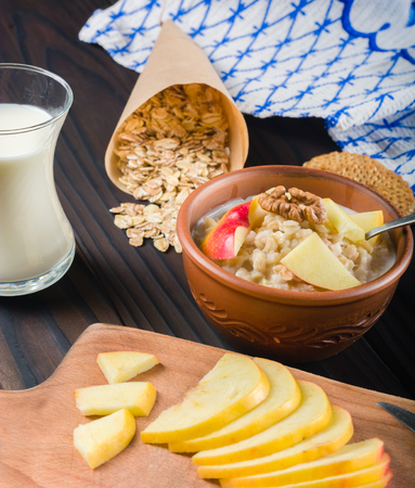 apple paper bag: Cooked porridge oatmeal in a bowl on a wooden dark background. Ingredients for cooking. Milk and napkin. Stock Photo