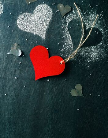 Card for Valentines Day. Red paper heart on a rope. Strict dark background.