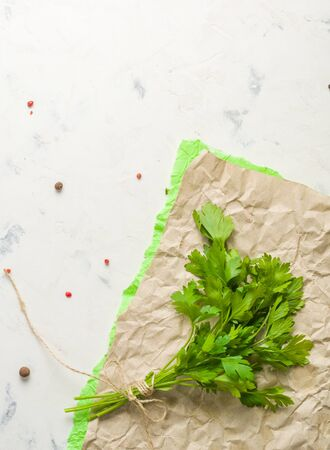 Bunch of parsley tied with string on a light stone background. Space for text.