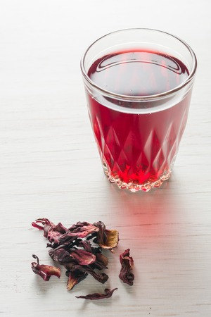 longevity medicine: Hibiscus tea in a glass mug on a wooden table among rose petals and dry tea custard. Copy space. Stock Photo