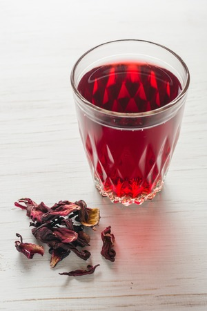 Hibiscus tea in a glass mug on a wooden table among rose petals and dry tea custard. Copy space. Stock Photo