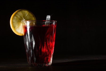 Transparent glass cup with hot hibiscus tea. The vapor from the top. Black background. Space for text