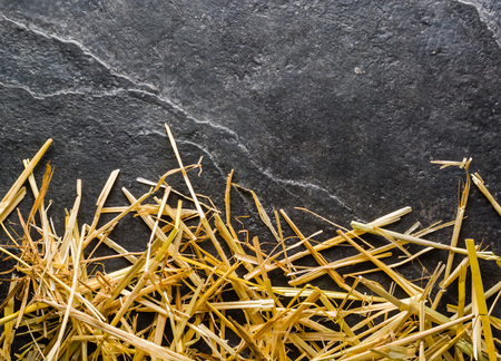 A bunch of yellow straw on the black background of an empty slab of slate. Place for text. Stock Photo