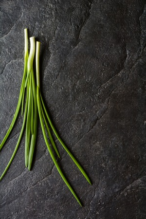 A bunch of green onion leaves on a background of black slate. Plenty of space for text. Stock Photo