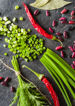 Arrangement of chives, onions, beans and dill on a black background stone slate. View from above. Stock Photo