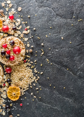 dietary fiber: Round Crisp on a black stone background. Rice grains, oatmeal flakes and buckwheat series. Berries and fruit top.