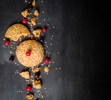 Oatmeal cookies are their pieces and crumbs with red berries on a black wooden background. Place for the text. Low key. Stock Photo
