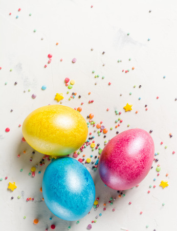 Easter background with multi-colored chicken eggs on a white stone slab. Place for the text.