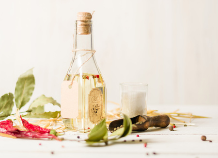 Vegetable oil in a bottle with seasonings and spices on a white wooden background. Place for the text.