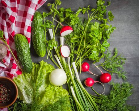 Variety of vegetables on a black wooden table with a red checkered cloth. View from above.