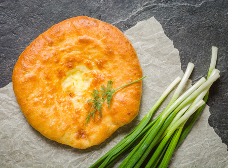 enrich: A large loaf of bread with green onions and dill on a black background. View from above. Stock Photo