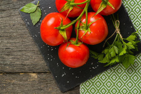 Branch with five ripe red tomatoes. Drops of water on ripe fruits. Green leaves and trunk. Copy space. Stock fotó