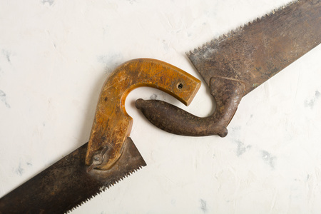 Large teeth of an old saw on wood. Sharp and uneven edges. Rusted surface. Light stone background. Copy space.